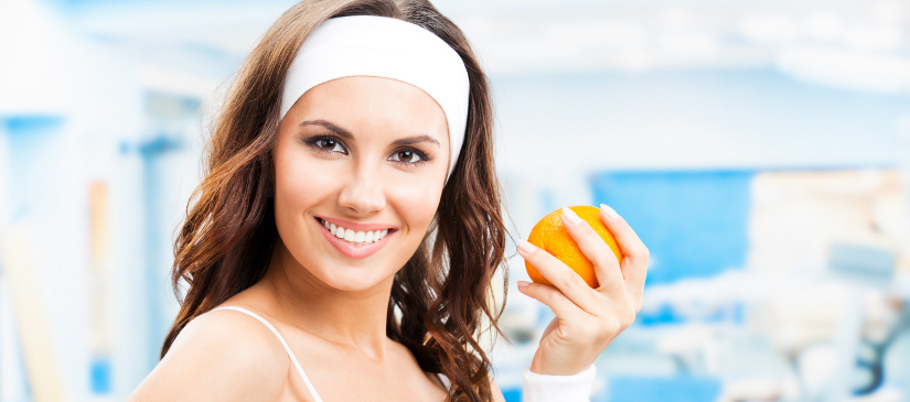 Cheerful young beautiful woman with orange, at fitness center or gym