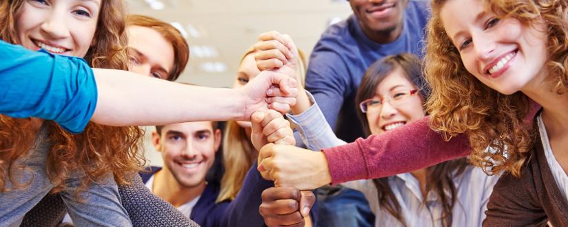 Studenten stapeln Fäuste für Zusammenarbeit und Teamwork in der Universität
