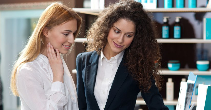 two woman friends looking at brochure at beauty salon desk