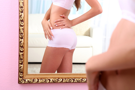 Young woman with slim body posing near mirror in room