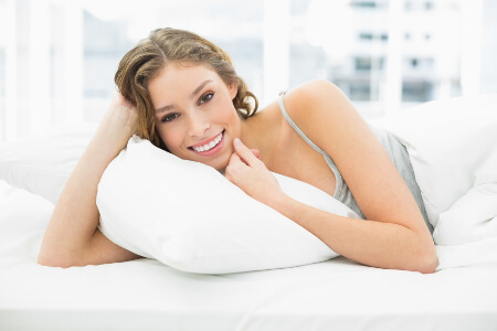 Peaceful content woman lying in her bed under the cover smiling at camera