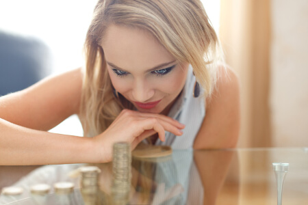 Happy blonde woman counting coin columns, gold digger, depth of field